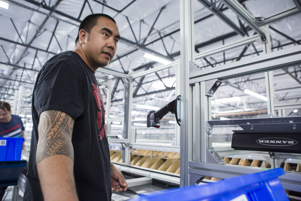 Warehouse employee Dustin Kula watches printed athletic logo apparel on a sorting belt at the Fanatics distribution center in North Las Vegas, Wednesday, Aug. 16, 2017. (Elizabeth Brumley/Las Vega ...