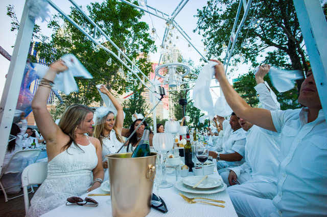 Attendees wave their tales before starting to eat during the Diner en Blanc pop-up picnic event at The Park in Las Vegas on Sunday, April 17, 2016. Chase Stevens/Las Vegas Review-Journal Follow @c ...