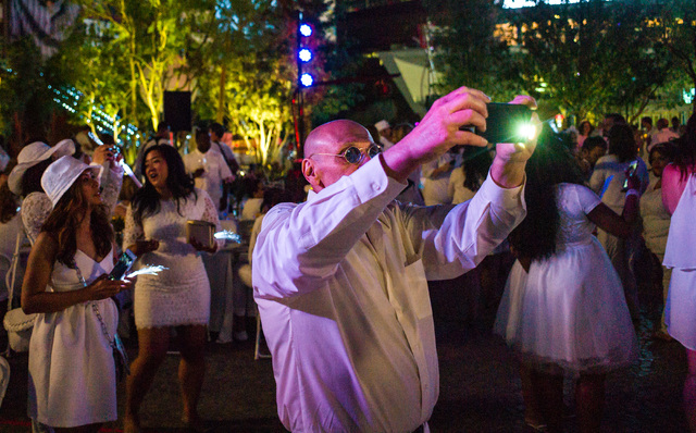 A man takes a photo as people dance during the Diner en Blanc pop-up picnic event at The Park in Las Vegas on Sunday, April 17, 2016. Chase Stevens/Las Vegas Review-Journal Follow @csstevensphoto