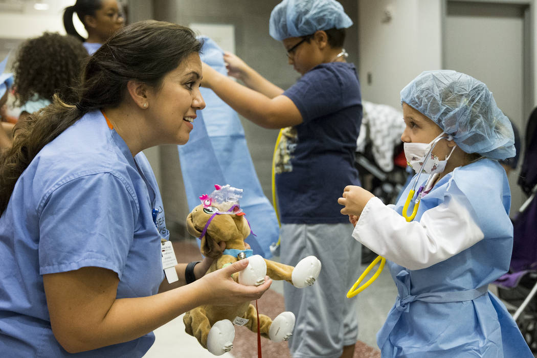 Jennifer Rivera, clinical system coordinator in the operating room, left, teaches Sierra Kreps, 4, how to check the heart beat of her stuffed animal during the Teddy Bear Clinic at Centennial Hill ...