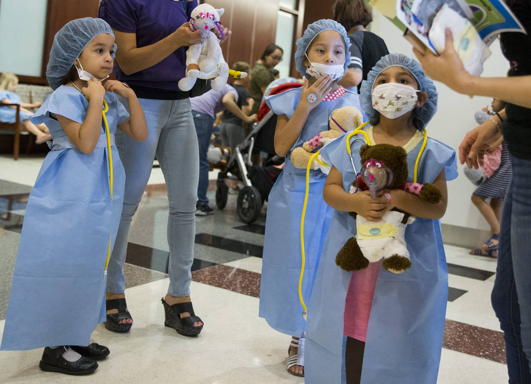 Sofia Ruiz, 5, from left, with her mother Liz, and Daniela Sebastian, 6, her sister Natalia, and their mother Joanna, during the Teddy Bear Clinic at Centennial Hills Hospital in Las Vegas on Wedn ...