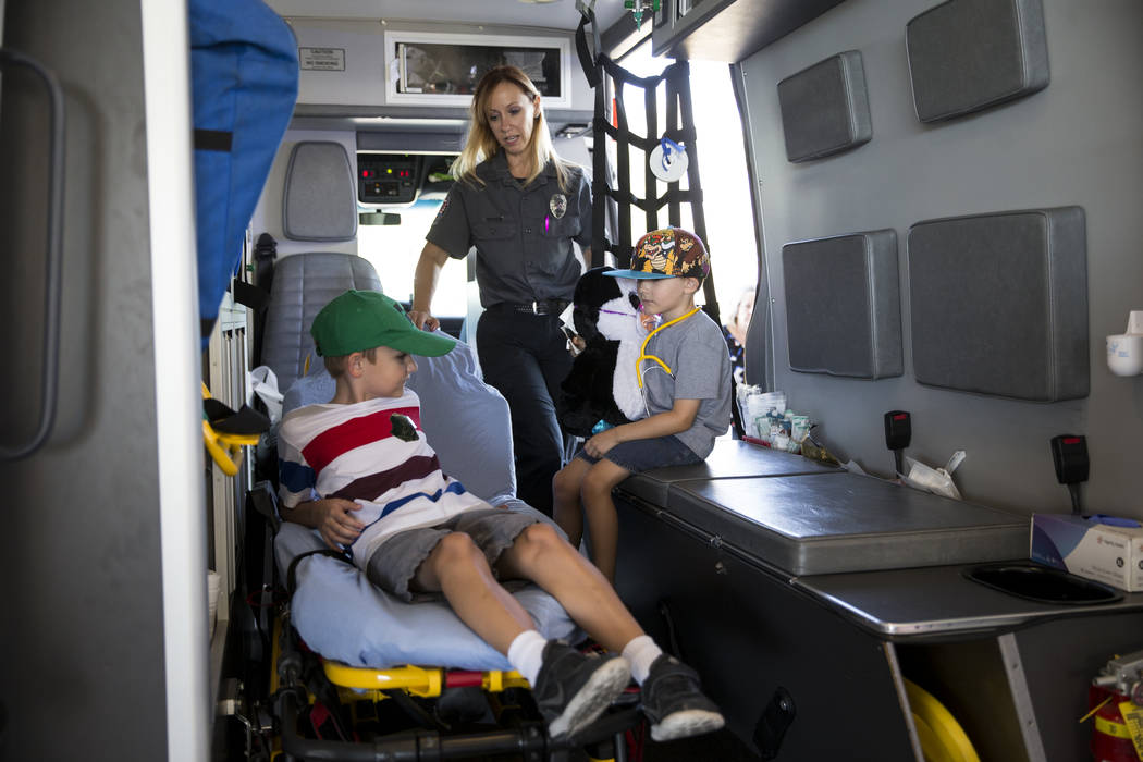 Melanie Bangle, paramedic with Community Ambulance, shows Noah Collins, 11, left, and his brother Logan, 5, inside an ambulance during the Teddy Bear Clinic at Centennial Hills Hospital in Las Veg ...