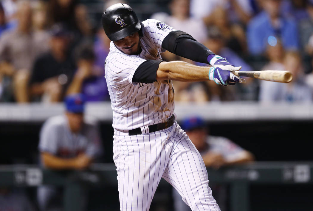 Colorado Rockies' Nolan Arenado follows through on a single that scored Charlie Blackmon with the winning run off New York Mets relief pitcher Hansel Robles duringw the ninth inning of a baseball  ...