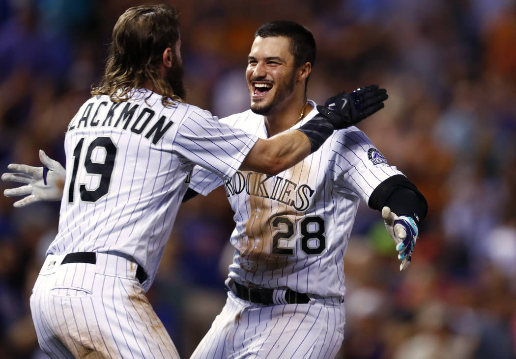 Colorado Rockies' Charlie Blackmon, left, hugs Nolan Arenado after Arenado's single drove in Blackmon with the winning run, off New York Mets relief pitcher Hansel Robles during the ninth inning o ...