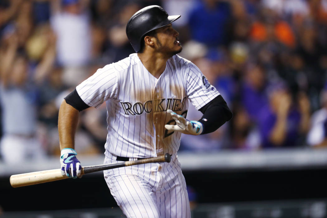 Colorado Rockies' Nolan Arenado watches his single that drove in Charlie Blackmon with the winning run, off New York Mets relief pitcher Hansel Robles during the ninth inning of a baseball game Tu ...