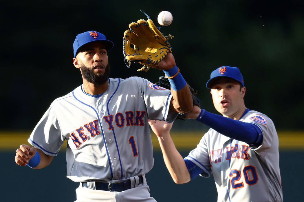 New York Mets shortstop Amed Rosario, front, catches the throw to force out Colorado Rockies' DJ Le Mahieu at second base on the front end of a double play hit into by Nolan Arenado to end the bot ...