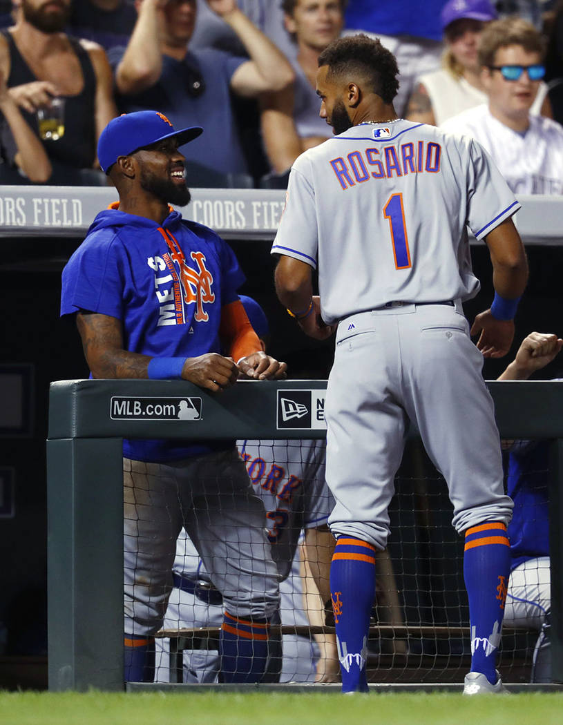 New York Mets' Jose Reyes, left, congratulates Amed Rosario, who had a hit in his debut in the majors, off Colorado Rockies reliever Scott Oberg duirng the eighth inning of the baseball game Tuesd ...