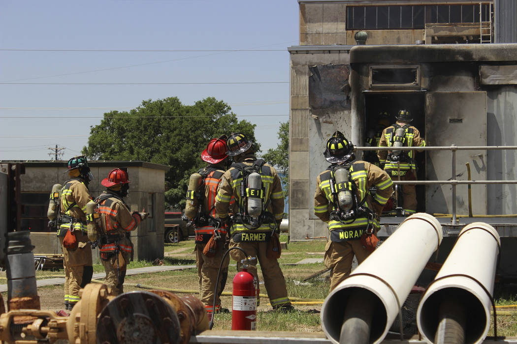 In this photo provide by the Bryan, Texas Fire Department, taken April 29, 2014, Bryan Texas firefighters stand outside the Bryan Texas Utilities Power Plant following an explosion and fire. Earle ...