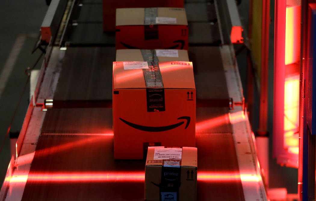 In this Tuesday, Aug. 1, 2017, photo, packages riding on a belt are scanned to be loaded onto delivery trucks at the Amazon Fulfillment center in Robbinsville Township, N.J. Amazon is holding a gi ...