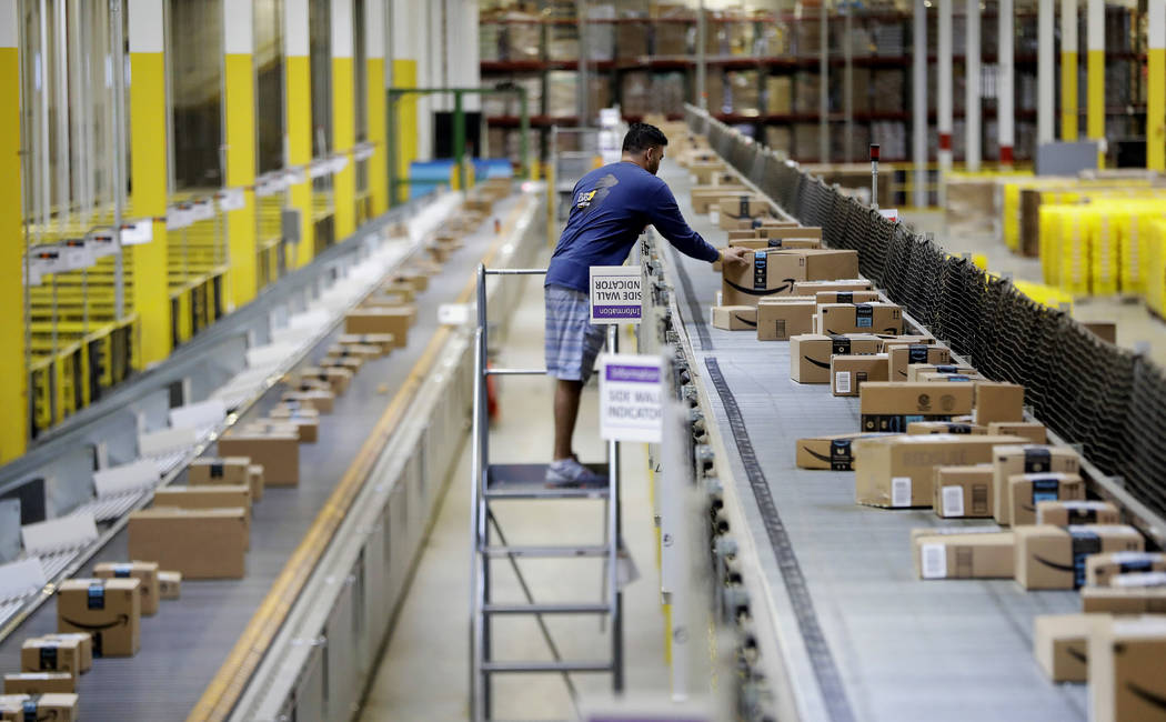 In this Tuesday, Aug. 1, 2017, photo, an Amazon employee makes sure a box riding on a belt is not sticking out at the Amazon Fulfillment center in Robbinsville Township, N.J. Amazon is holding a g ...