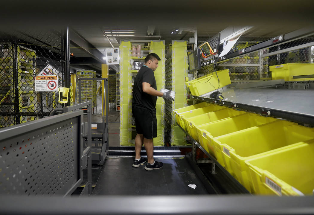 In this Tuesday, Aug. 1, 2017, photo, an Amazon employee sorts items brought to him by robotic shelves at the Amazon Fulfillment center in Robbinsville Township, N.J. Amazon is holding a giant job ...