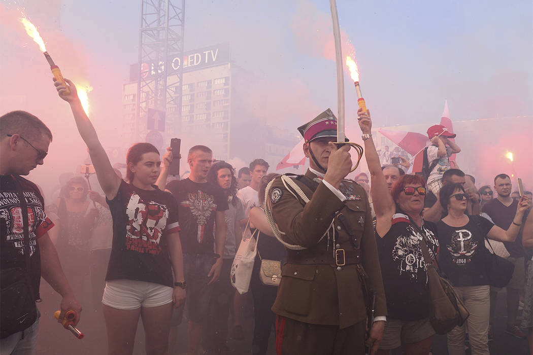 People stand on the city's main intersection holding burning flares to commemorate the 73rd anniversary of the 1944 Warsaw Uprising in Warsaw, Poland, Tuesday, Aug. 1, 2017. Thousands of residents ...