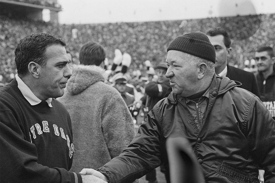 In this Nov. 19, 1966, file photo, Notre Dame football coach Ara Parseghian, left, shakes hands with Michigan State coach Duffy Daugherty after their 10-10 tie in East Lansing, Mich. Parseghian di ...