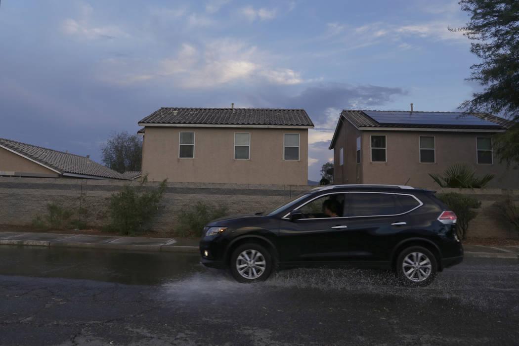 A car drives through a flooded street on Wetlands Park Lane near Clark County Wetlands Park in Las Vegas, Wednesday, Aug. 2, 2017. Gabriella Angotti-Jones Las Vegas Review-Journal @gabriellaangojo