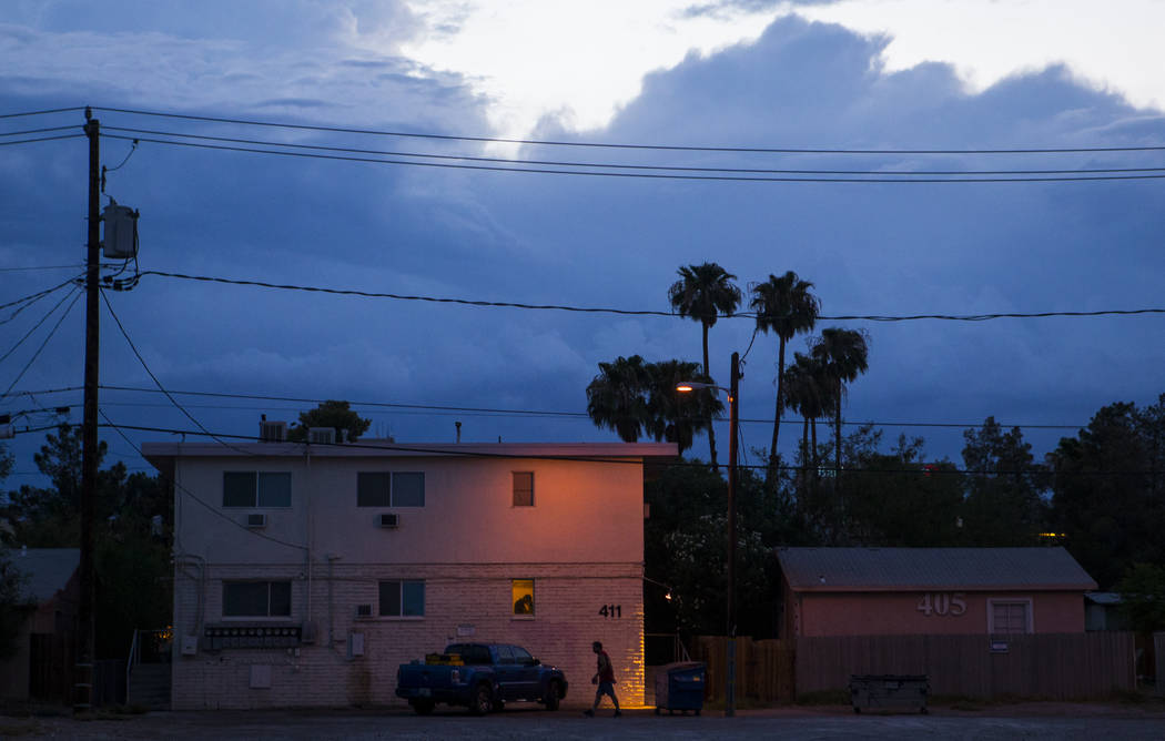 A man is silhouetted against an apartment building along Maryland Parkway as clouds fill the sky  in Las Vegas on Wednesday, Aug. 2, 2017. Chase Stevens Las Vegas Review-Journal @csstevensphoto