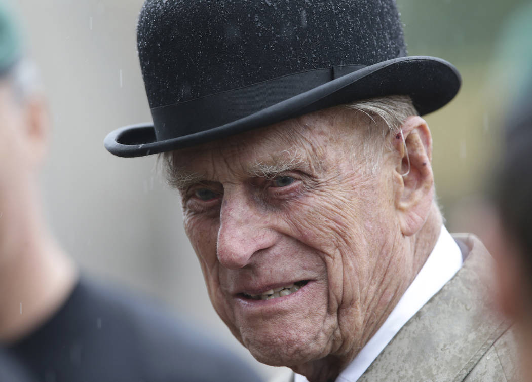 Britain's Prince Philip, in his role as Captain General of the Royal Marines, talks to troops as he attends a Parade on the forecourt of Buckingham Palace, in central London, as it rains Wednesday ...