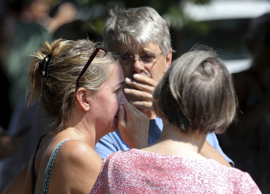 Former Minnehaha Academy employees Elizabeth Van Pilsum, left, and Rick Olson, center, react after an explosion at the school Wednesday, Aug. 2, 2017, in Minneapolis.Several people are unaccounted ...