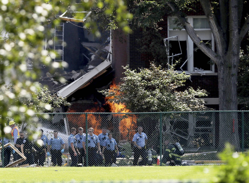 Emergency personnel move away as a gas fire continues to burn following an explosion at Minnehaha Academy Wednesday, Aug. 2, 2017, in Minneapolis. Several people are unaccounted for after an explo ...