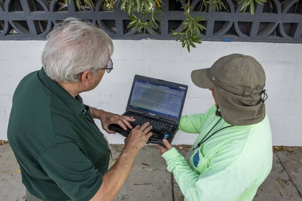 Lyle Mariam, left, a mechanical engineer with the Las Vegas Valley Water District, and Tony Hamer, an asset management technician, show data on a laptop from a new water pressure recording system  ...