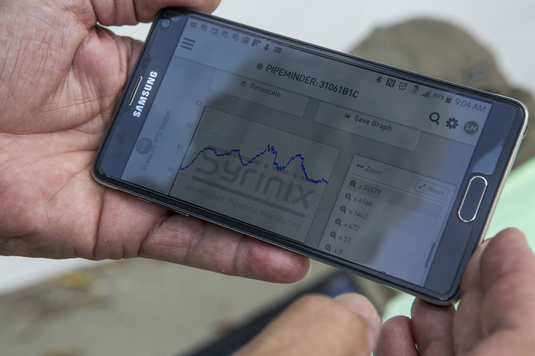 Lyle Mariam, a mechanical engineer with the Las Vegas Valley Water District, shows data on his phone from the district's newest technology, a water pressure recording system called Syrinix, at a h ...