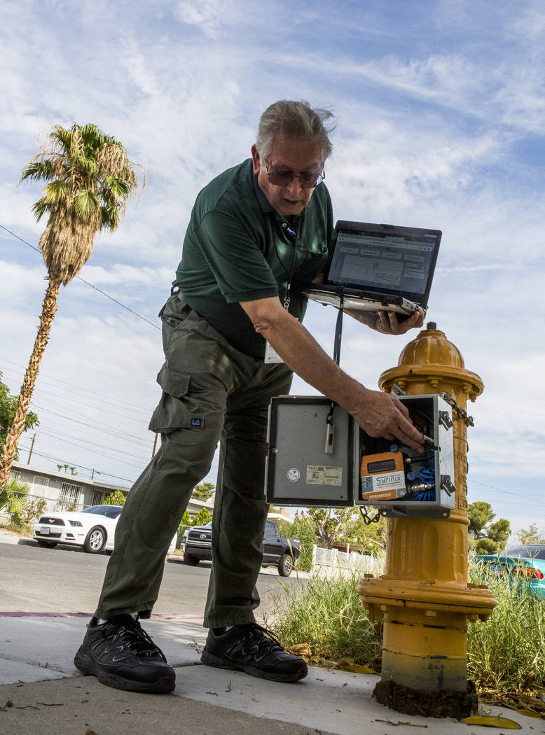 Lyle Mariam, a mechanical engineer with the Las Vegas Valley Water District, shows the district's newest technology, a water pressure recording system called Syrinix, at a hydrant near Sahara Aven ...