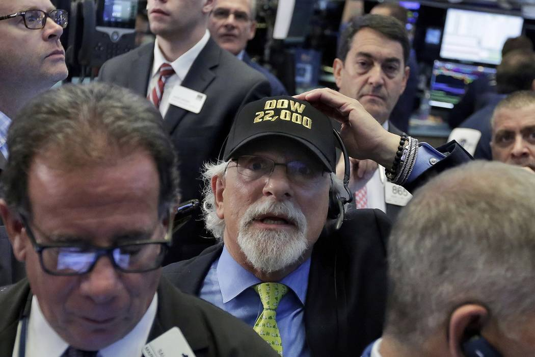 Trader Peter Tuchman, center, wears a Dow 22,000 hat as he works on the floor of the New York Stock Exchange, Wednesday, Aug. 2, 2017. A big gain from Apple Wednesday morning sent the Dow Jones in ...
