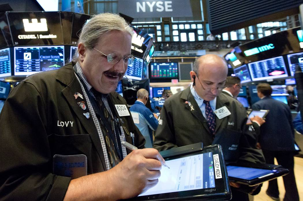 Traders Steve Lovejoy, left, and Andrew Silverman work on the floor of the New York Stock Exchange, Wednesday, Aug. 2, 2017. A big gain from Apple Wednesday morning sent the Dow Jones industrial a ...