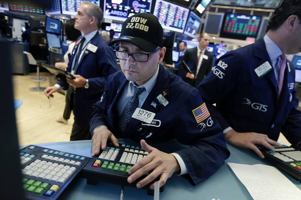 "Specialist Mario Picone wears a ""Dow 22,000"" hat as he works at his post on the floor of the New York Stock Exchange, Wednesday, Aug. 2, 2017. A big gain from Apple Wednesday morning sent the Dow  ..."