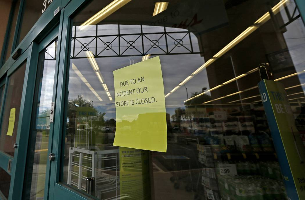 Signs posted at the entrance of a local Walgreens let possible customers know that the store remains closed Wednesday, Aug. 2, 2017, in Phoenix, after a customer at the drugstore shot and killed a ...