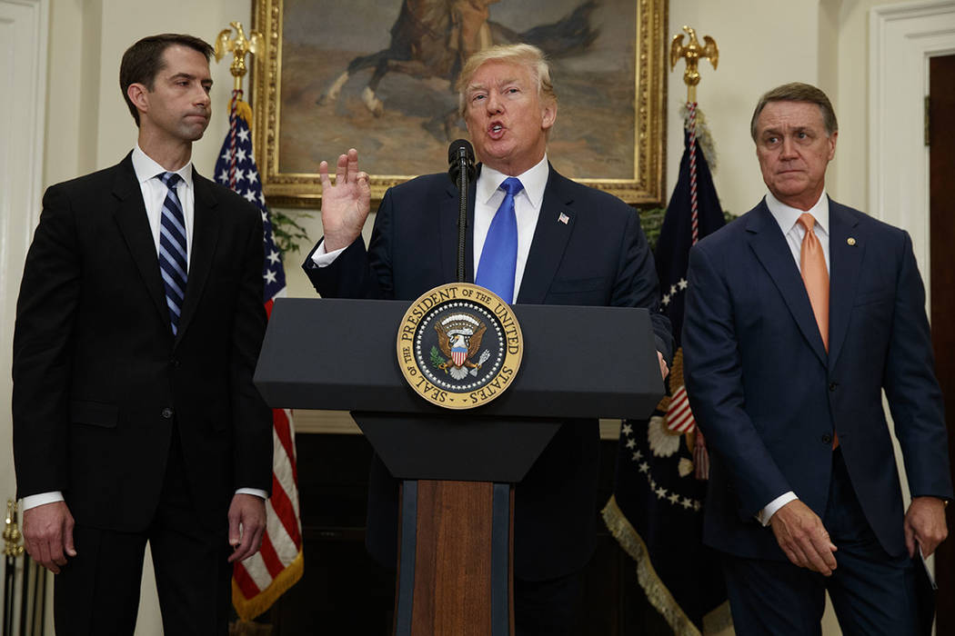 President Donald Trump, flanked by Sen. Tom Cotton, R- Ark., left, and Sen. David Perdue, R-Ga., speaks in the Roosevelt Room of the White House in Washington, Wednesday, Aug. 2, 2017, during the  ...