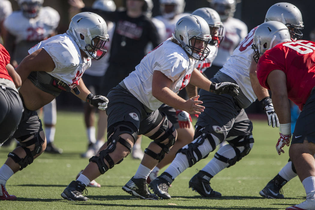 UNLV offensive lineman Jackson Reynolds, center, looks to block defensive lineman Ammir Aziz while scrimmaging during training camp at Rebel Park on Monday, Aug. 14, 2017.  Patrick Connolly Las Ve ...