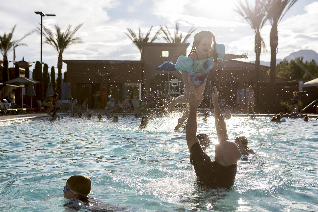 Mike Summers throws his daughter Savannah, 4, in the air at Vistas Pool on Thursday, Aug. 3, 2017, in Las Vegas. Visitors enjoyed a dip in the pool during the Blizzard Beach Splash Nite, a winter  ...