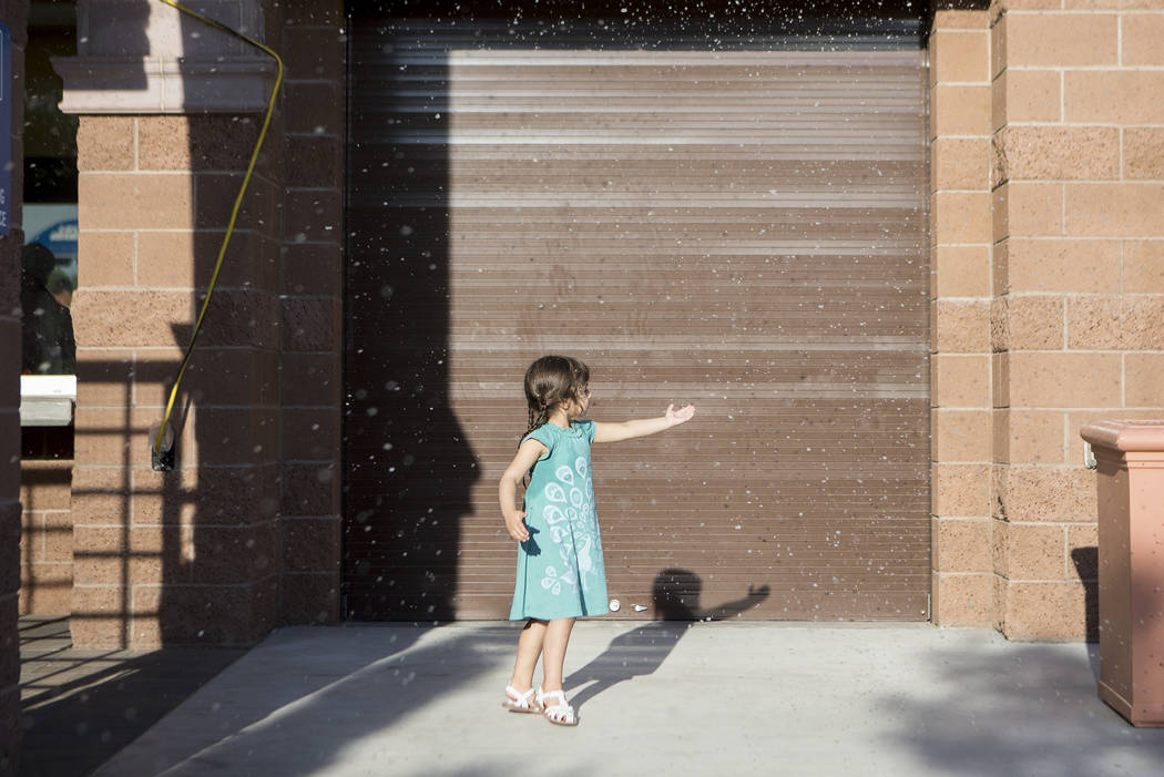 Skye Junyent reaches for fake snow outside Vistas Pool on Thursday, Aug. 3, 2017, in Las Vegas. Visitors enjoyed a dip in the pool during the Blizzard Beach Splash Nite, a winter wonderland themed ...