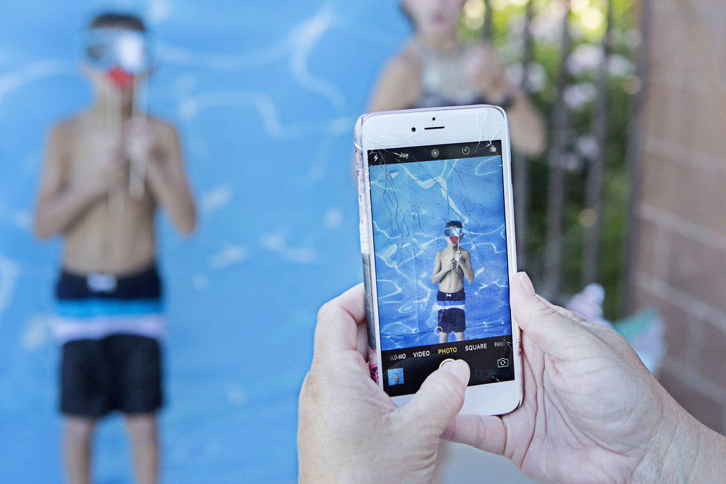 Dionne Rodgers holds her phone while she takes a photo of her son Colton Rogers, 8,  at Vistas Pool on Thursday, Aug. 3, 2017, in Las Vegas. Visitors enjoyed a dip in the pool during the Blizzard  ...