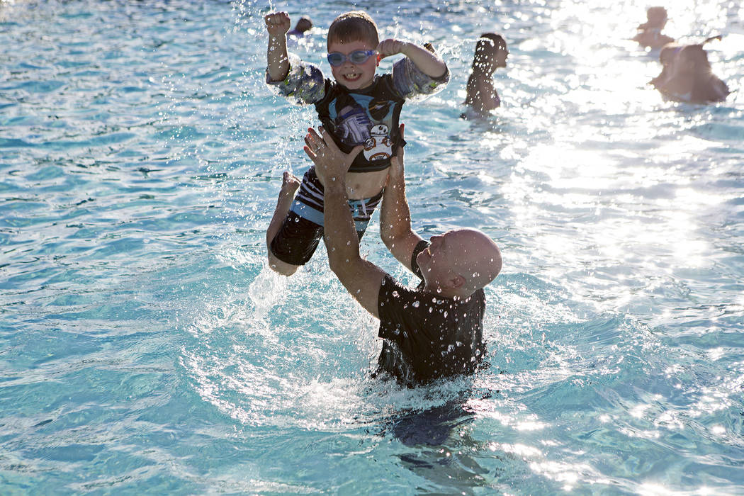 Mike Summers tosses his son Carson Summers, 7, up in the air at Vistas Pool on Thursday, Aug. 3, 2017, in Las Vegas. Visitors enjoyed a dip in the pool during the Blizzard Beach Splash Nite, a win ...