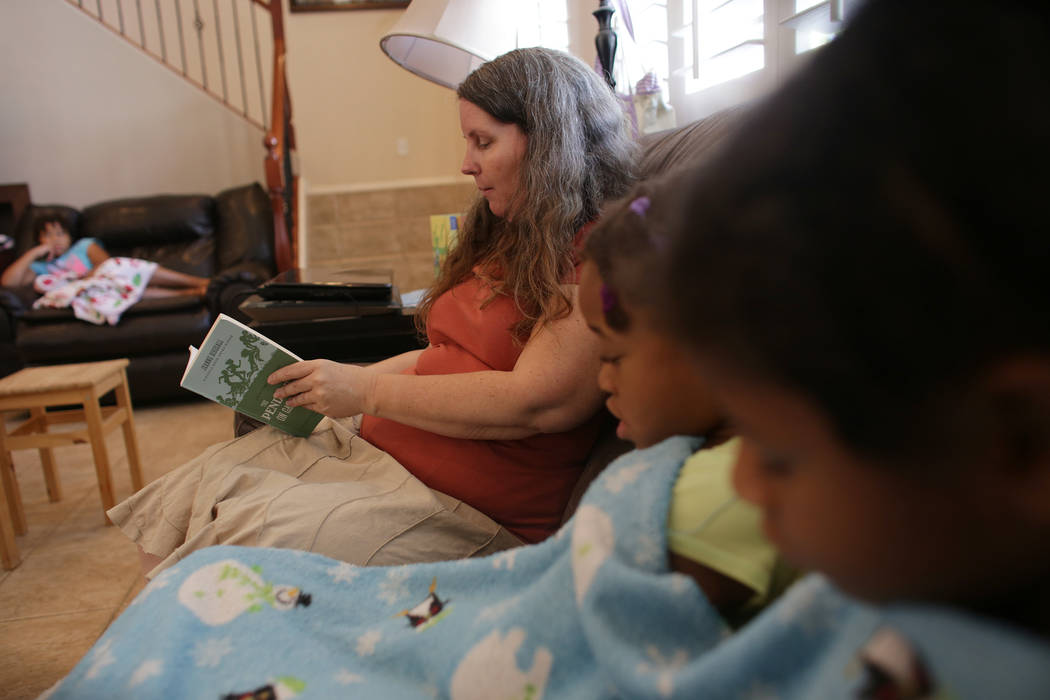 Tami Prince reads to her daughters Armani Prince, 6, and Marcella Prince, 8, on Wednesday, Aug. 2, 2017, at their home in Las Vegas. Tami and her husband Kevin choose to home-school all nine of th ...