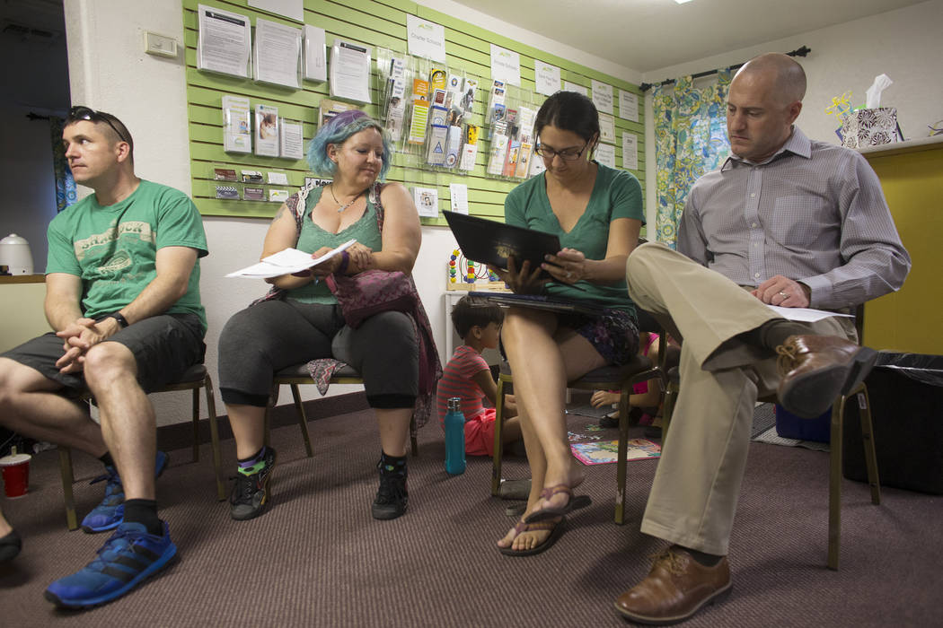 Nate Cothran, from left, Nicole Sligar, Shanna Groppenbacher, and Jonathan Groppenbacher look over handout material at an introduction to home-school session put on by RISE on Thursday, May 25, 20 ...