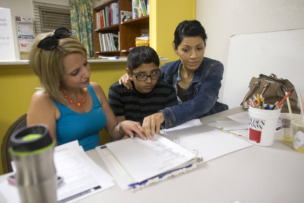 Lizbeth Ruiz, from left, Isaias Manrique, 13, and his mom Maggie Manrique look over handout material at an introduction to home-school session put on by RISE on Thursday, May 25, 2017, at the RISE ...