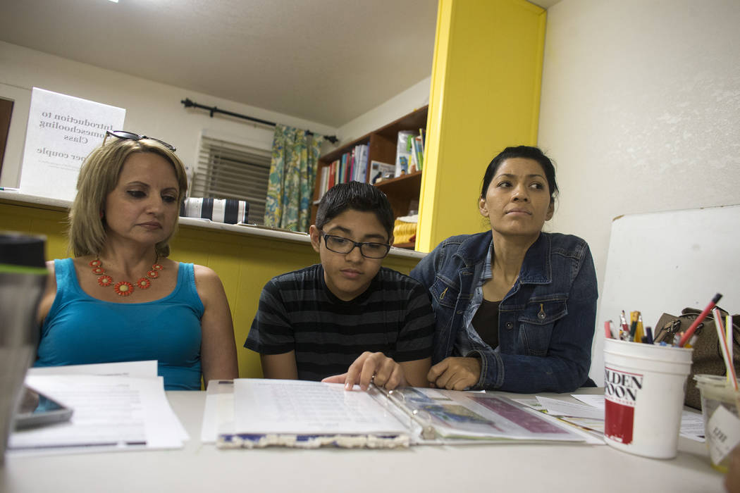 Lizbeth Ruiz, from left, Isaias Manrique, 13, and his mom Maggie Manrique look at handout material at an introduction to home-school session put on by RISE on Thursday, May 25, 2017, at the RISE R ...