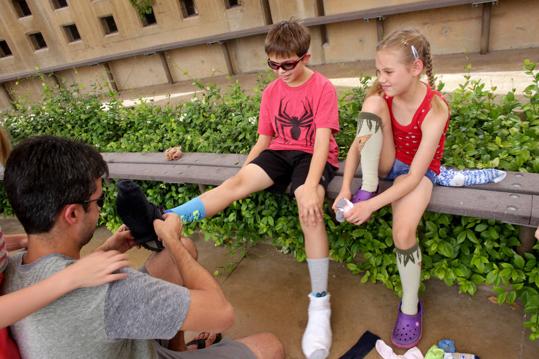 Justin Kattal, left,  helps put a sock over the shoes of his son Caleb, 9, as he sits next to Doris Moore, 8, at Springs Preserve on Thursday, June 8, 2017, in Las Vegas. They are a part of a home ...