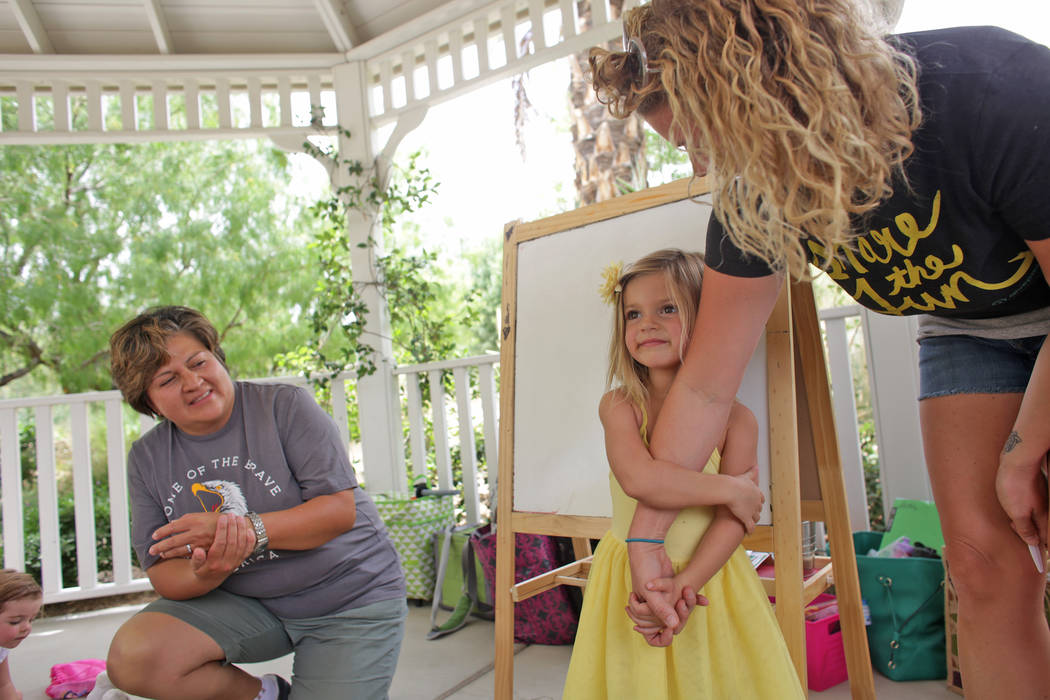Sandra Stewart, left,  watches as Laura Runco, right, helps her daughter Lily Runco, 4, introduce herself to the a home-school group called Wise Owls at Springs Preserve on Thursday, June 8, 2017, ...