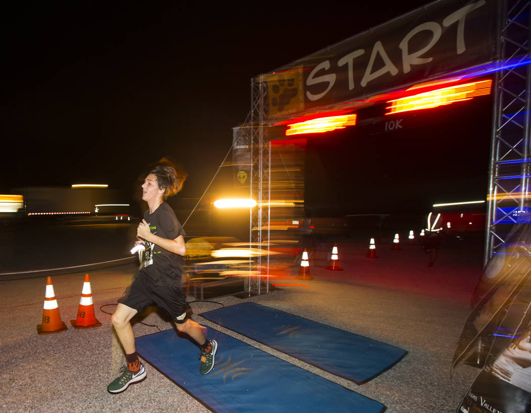Foster Cottingham of Las Vegas crosses the finish line first as park of the 5k race during the Extraterrestrial Full Moon Midnight Marathon in Rachel on Saturday, Aug. 5, 2017. The event featured  ...