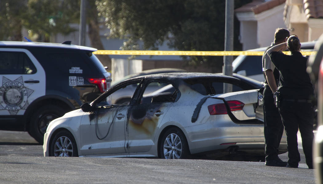 Crime scene personnel and detectives investigate a burned car that contained a body in the 6600 block of Castor Tree Way, near Rainbow Boulevard and Cheyenne Avenue, on Thursday, June 21, 2017. Ri ...