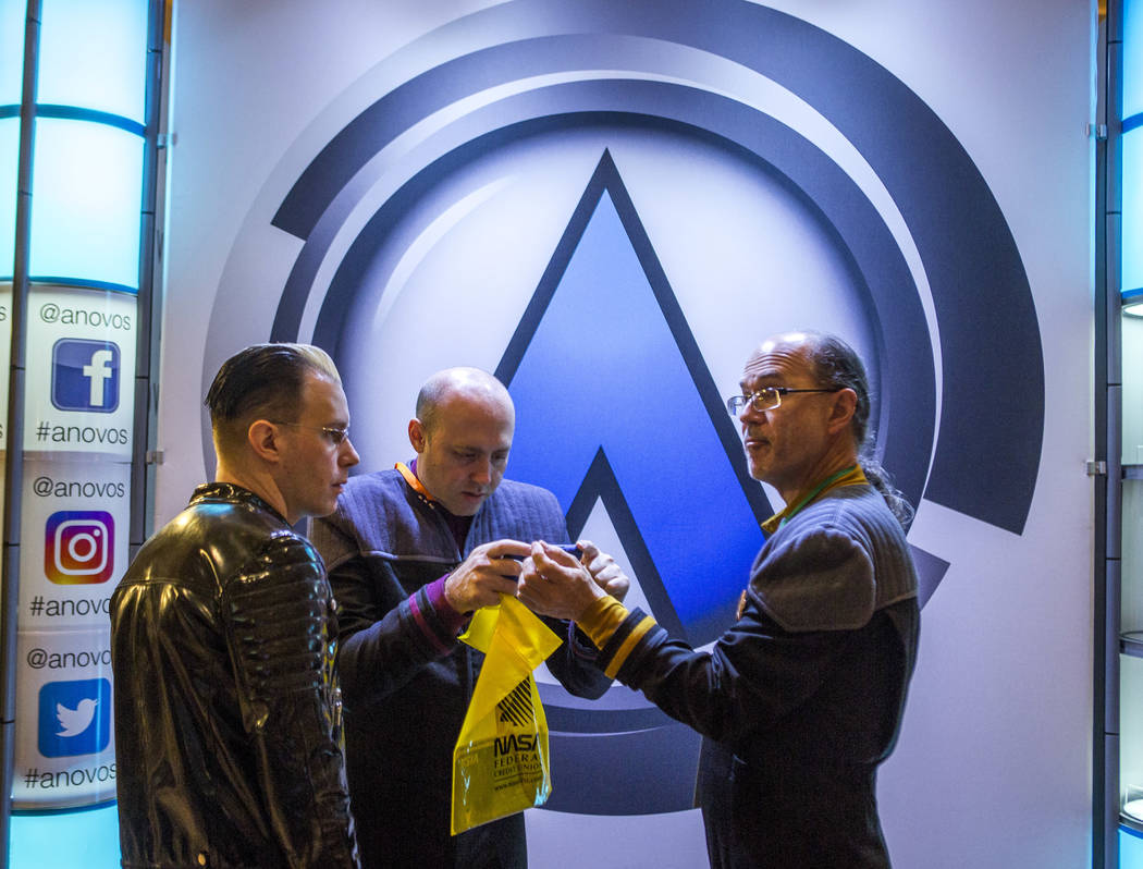 Casey Baldwin, left, and David Coblentz, center, check out James Holmes' costume, which was used in a Star Trek movie, during the Official Star Trek Convention at the Rio Convention Center on Thur ...