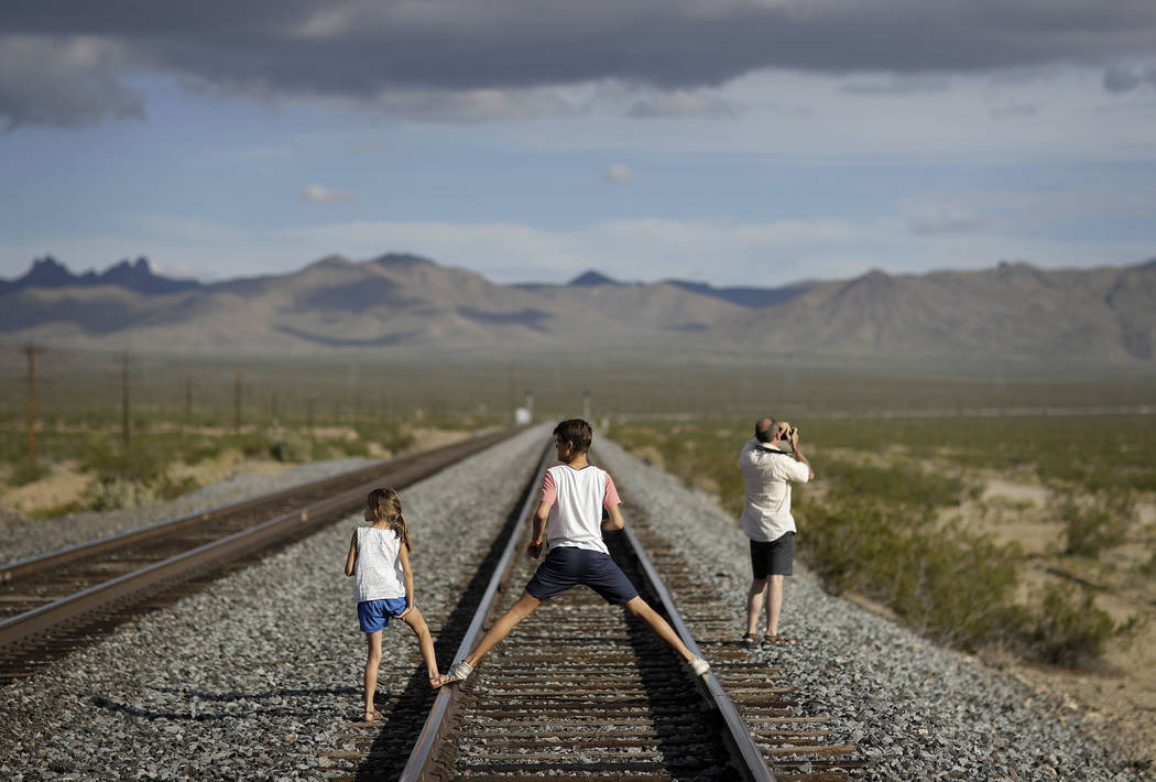 A family walks along train tracks, Thursday, Aug. 3, 2017, in Nipton, Calif. One of the nation's largest cannabis companies announced it has bought the entire 80 acre California desert town of Nip ...