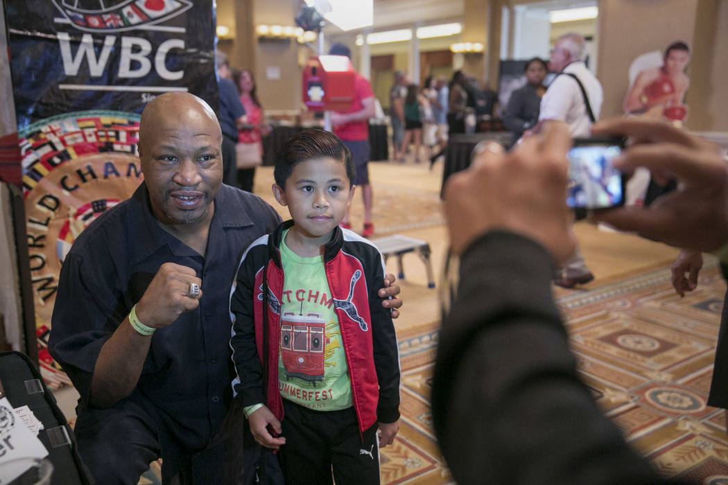 World Boxing Organization Heavyweight Champion Ray Mercer, left, poses for a picture with Ethan Calaguas, 10, of San Francisco during a Fan meet-and-greet before the 2017 Nevada Boxing Hall of Fam ...