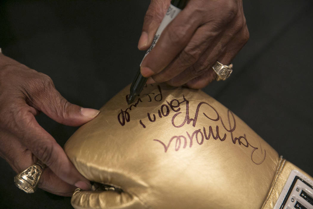 """Pernell """"Sweet Pea"""" Whitaker signs a fan's boxing glove during a fan meet-and-greet before the 2017 Nevada Boxing Hall of Fame ceremony in The Palace Ballroom at Caesars Palace i ..."""
