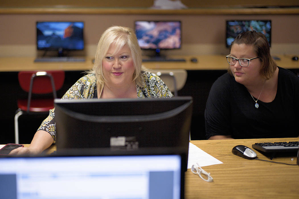 In this Thursday, July 27, 2017, photo, Cheryl Bast, left, is accompanied by her daughter Liz Pierson, as she works on an application for a position with Omaha Public Schools, during a job fair he ...