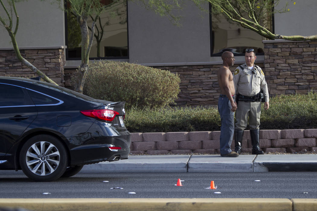 Police talk to a man at the scene of an auto-pedestrian crash, Friday, Aug. 4, 2017, at the intersection of West Tropicana Avenue and South Durango Drive. (Richard Brian/Las Vegas Review-Journal)  ...
