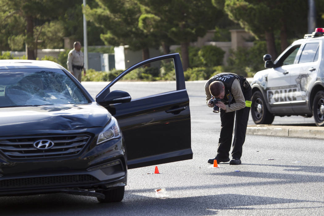 A crime scene investigator photographs the scene of an auto-pedestrian crash, Friday, Aug. 4, 2017, at the intersection of West Tropicana Avenue and South Durango Drive. (Richard Brian/Las Vegas R ...